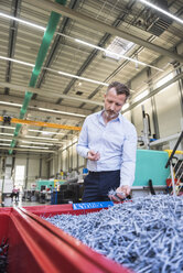 Man in factory examining shred in container - DIGF02090