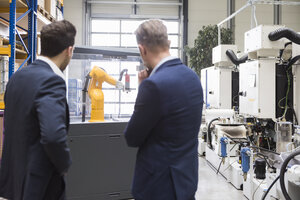 Two businessmen in factory shop floor looking at industrial robot - DIGF02096