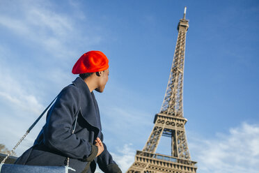 France, Paris, young woman wearing red beret in front of Eiffel Tower - KIJF01382