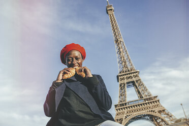 France, Paris, young woman eating two croissants in front of Eiffel Tower - KIJF01385