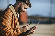 Spain, Cadiz, Young man at the harbour using smartphone and digital tablet - KIJF01396