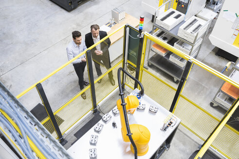 Two businessman observing industrial robots in factory - DIGF02102