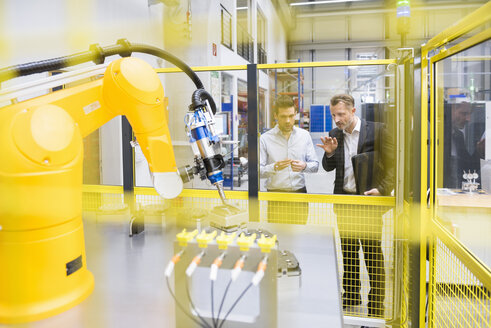 Two businessman observing industrial robots in factory - DIGF02105