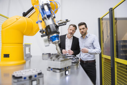 Two businessman observing industrial robots in factory - DIGF02108