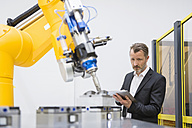 Mature businessman controlling industrial robots with digital tablet - DIGF02111