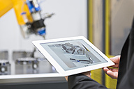 Mature businessman controlling industrial robots with digital tablet - DIGF02114