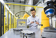Young businessman checking automated production in factory - DIGF02117