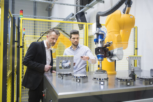 Two businessman observing industrial robots in factory - DIGF02120