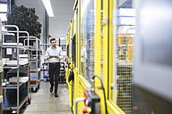 Young businessman checking automated production in factory - DIGF02123