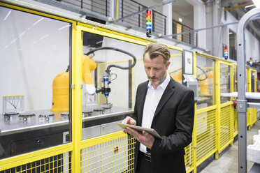 Mature businessman controlling industrial robots with digital tablet - DIGF02129