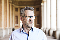 Portrait of content businessman with stubble wearing glasses - FMKF03964