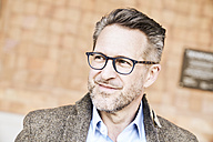 Portrait of smiling man with stubble wearing glasses - FMKF03970
