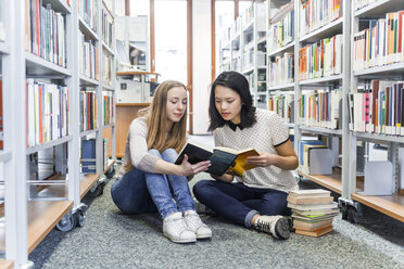 Two teenage girls sitting on the floor in a public library reading in a book - TCF05379