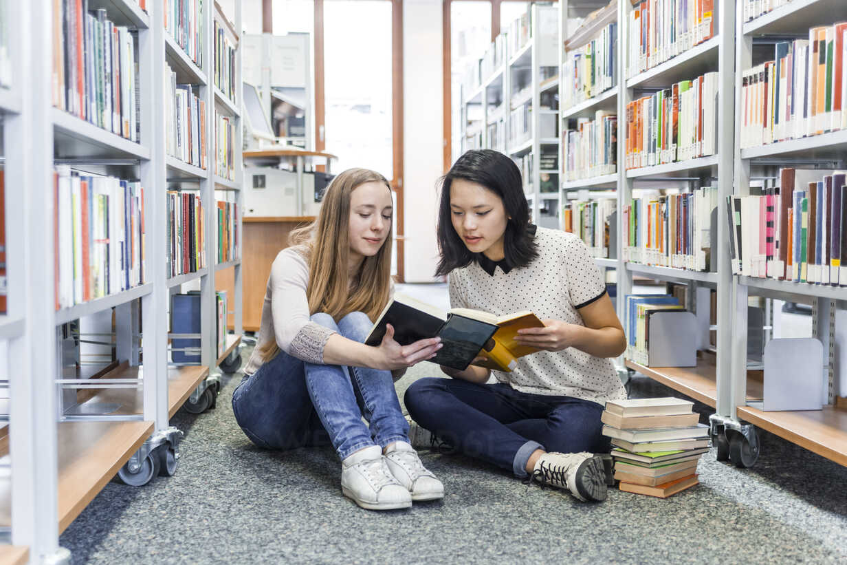 Two teenage girls sitting on the floor in a public library reading in a book - TCF05379 - Tom Chance/Westend61