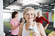 Group of fit seniors in gym taking a break, drinking refreshment - HAPF01514