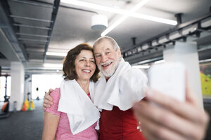 Fit senior couple taking selfies with smart phone in gym - HAPF01517