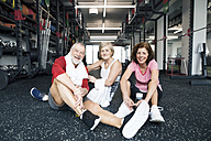 Group of fit seniors resting after working out in gym - HAPF01526