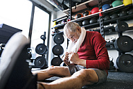 Exhausted senior man sitting on the floor after working out in gym - HAPF01529