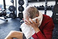 Exhausted senior man sitting on the floor after working out in gym - HAPF01532