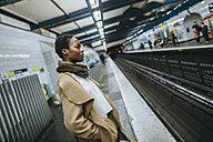 Young woman waiting at subway station platform - KIJF01403