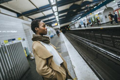Young woman waiting at subway station platform - KIJF01403