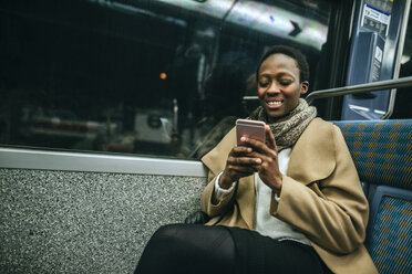 Portrait of smiling young woman looking at cell phone in underground train - KIJF01409