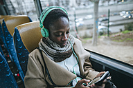 Young woman in a bus listening music with headphones while looking at cell phone - KIJF01412