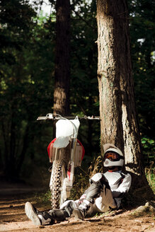 Italy, Motocross biker taking a break in Tuscan forest - FMOF00225