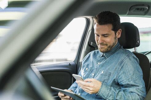Businessman sitting in car using smartphone and digital tablet - UUF10347
