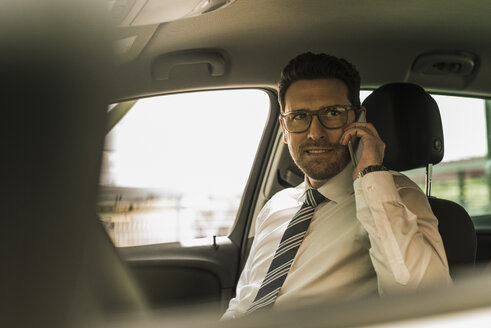 Successful businessman sitting in car talking on the phone - UUF10350