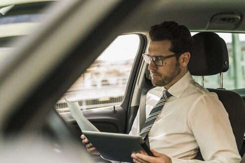 Successful businessman sitting in car using digital tablet - UUF10353