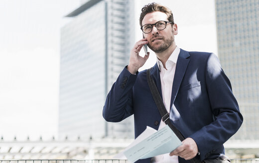 Businessman standing on parking level, making a call with documents in hands - UUF10365