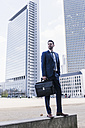 Businessman standing on wall, carrying briefcase - UUF10368
