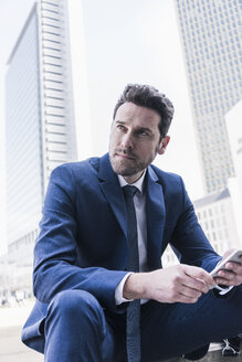 Businessman sitting in the city using smart phone - UUF10371