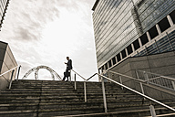 Businessman leaning on railing on top of stairs reading messages - UUF10377