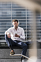 Businessman sitting in front of office building, wearing headphones - UUF10383