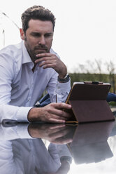 Businessman using digital tablet outdoors - UUF10386