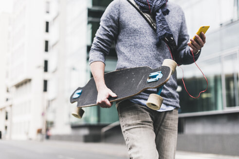 Businessman carrying skateboard, using smartphone and earphones - UUF10395