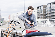 Businessman in the city with bicycle using smartphone and earphones - UUF10407