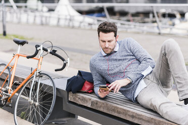 Businessman in the city with bicycle using smartphone and earphones - UUF10410
