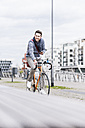 Businessman riding bicycle in the city, while using smartphone and earphones - UUF10413