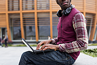 Man with headphones sitting on bench using laptop, partial view - MAUF01045