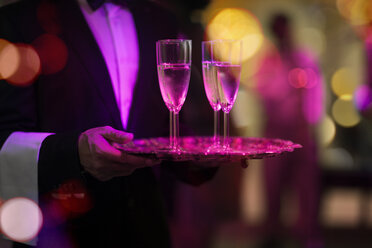 Waiter with tray serving champagne glasses on a party - ZEF13565