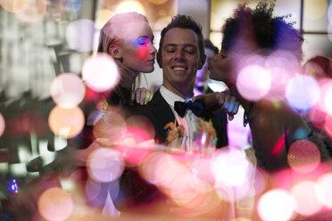 Two women kissing man in tuxedo on a party - ZEF13583
