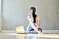 Pensive young woman sitting on the floor with laptop - FMKF03984