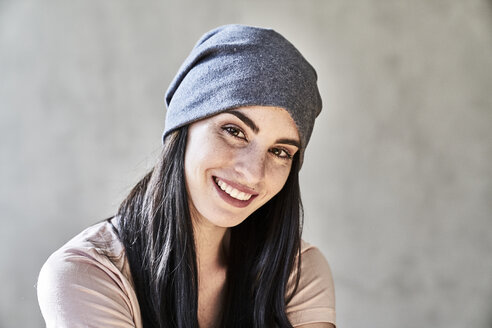 Portrait of smiling young woman wearing beanie - FMKF03987