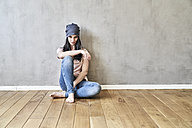 Young woman sitting on the floor in sparse room - FMKF03990