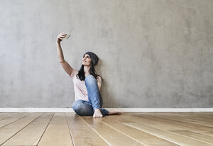Smiling young woman sitting on the floor taking a selfie - FMKF03993
