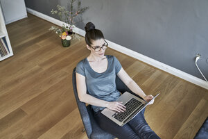 Young woman using laptop at home - FMKF04014