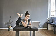 Young woman lying on lounge using laptop - FMKF04017